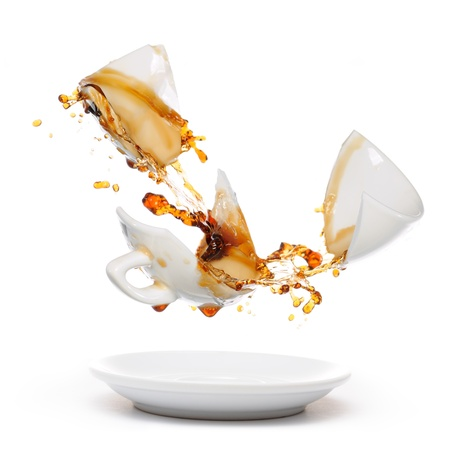 Broken coffee mug with splash of coffee  Isolated on white