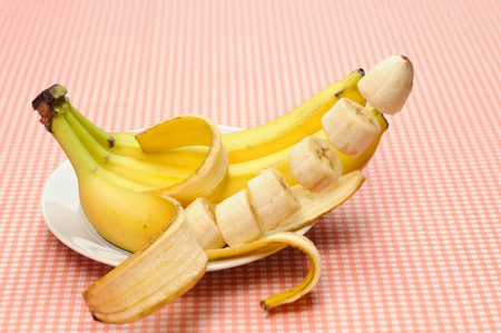 Banana peeled and slices are flying or floating photo