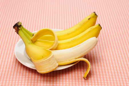 Three bananas on the plate  One of them is peeled Stock Photo