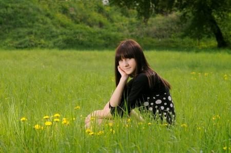 Girl sitting on green grass among the dandelions photo