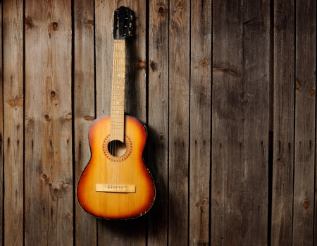 country music: The guitar hanging on the old wooden wall Stock Photo