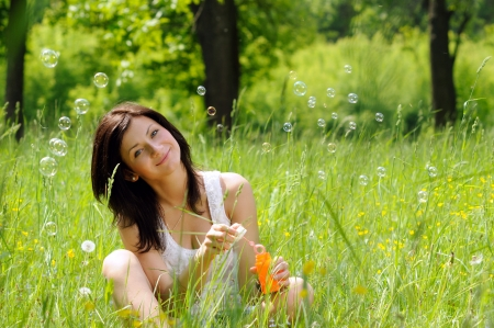 Portrait of young girl inflating soap bubbles on green meadow photo