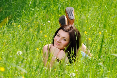 Girl lying on green grass and looking to the camera photo