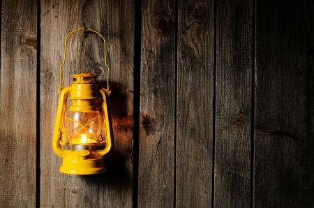 candil: La l�mpara de queroseno vieja colgada en la pared de madera Foto de archivo