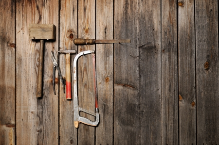 Old work tools hang on the wooden wall  With copyspace photo