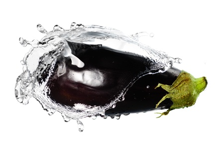 Ripe eggplant in splash of water isolated on white background photo