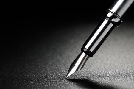 pluma de escribir antigua: Pluma vieja en un fondo negro con textura