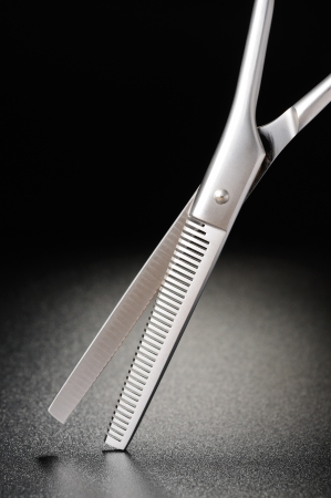 Professional hairdressing scissors on a black matt background