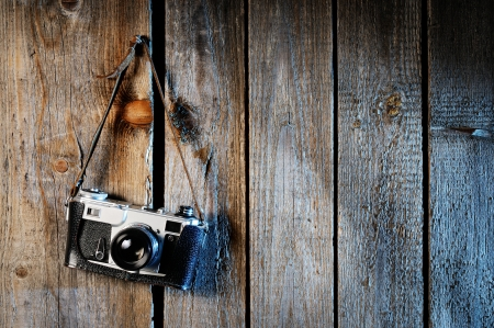 Old camera on weathered wooden background Stock Photo