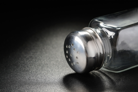 Empty pepper or salt shaker on a black background photo