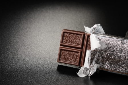 unwrapped: Open bar of chocolate on a black textured background