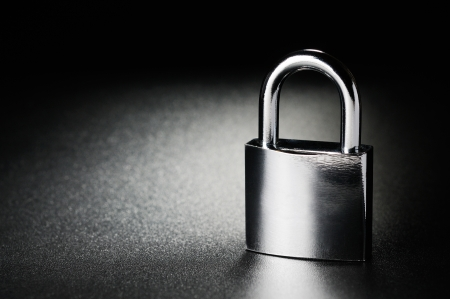 black and white lock: Steel padlock on the black textured background