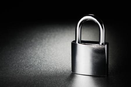 Steel padlock on the black textured background