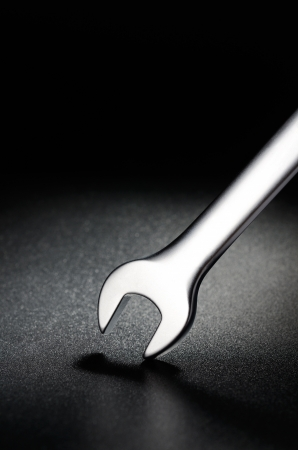 Steel wrench on a black textured background Stock Photo - 15284000