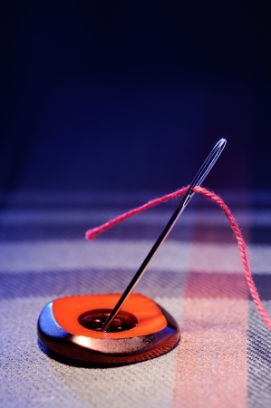 Needle and thread on a checkered fabric Stock Photo - 15659662