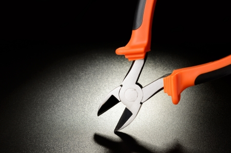 Orange wire cutter on black matte surface Stock Photo - 17319258