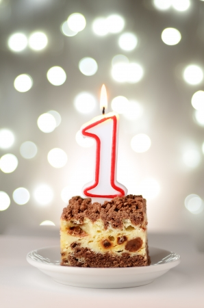 Holiday cake with a candle in the shape of the number one photo