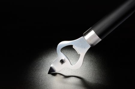 Bottle opener on black grained surface Stock Photo - 17616913