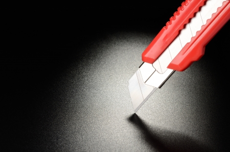 Utility knife, office knife on black grained surface Stock Photo - 17621048