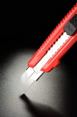 Utility knife, office knife on black grained surface Stock Photo - 17771957