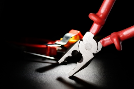 Combination Pliers on the black grained surface  Selective focus Stock Photo - 17987165