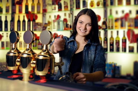 Bartender woman pours the beer into a glass Stock Photo