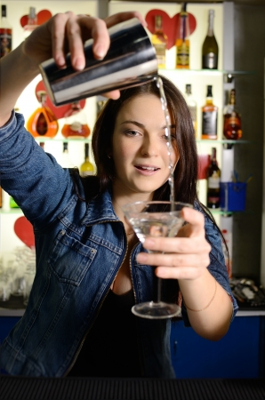 pours: Bartender woman pours the cocktail into a glass Stock Photo