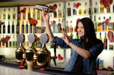 Bartender woman with a metal shaker in hand