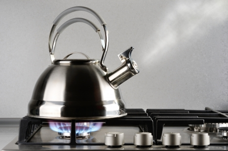 Tea kettle with boiling water on gas stove photo