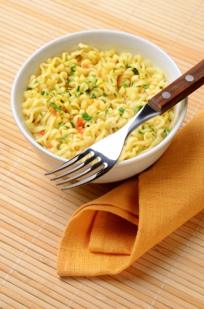 Instant noodles cooked in a bowl with a fork Stock Photo