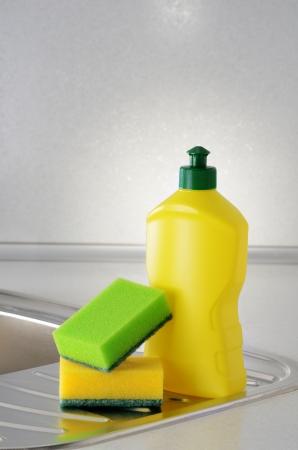 Dishwashing liquid with a sponge on kitchen sink