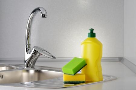 lavar platos: Detergentes con una esponja en la pileta de la cocina Foto de archivo