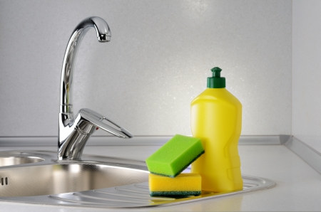 dishwashing: Dishwashing liquid with a sponge on kitchen sink