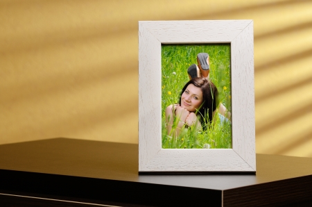 Girls portrait in a photo frame, standing on a table Stock Photo - 19062627