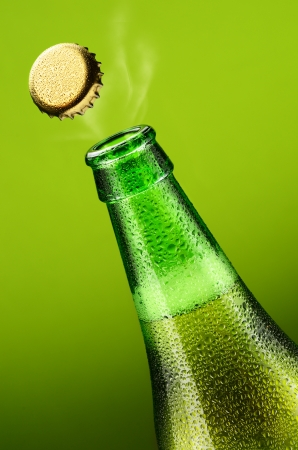 Bottle of beer with opening lid on a green background photo