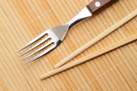 Chopsticks and a fork on the mat  Choice concept 版權商用圖片