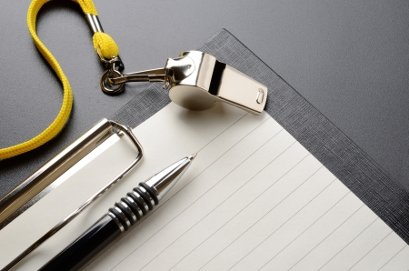 Metal sport whistle with pen and paper sheet Stock Photo