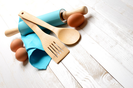 Cooking concept. Eggs and kitchen tools on white wooden table.