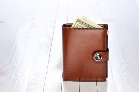 Brown leather wallet with one hundred dollar bills on white wooden table