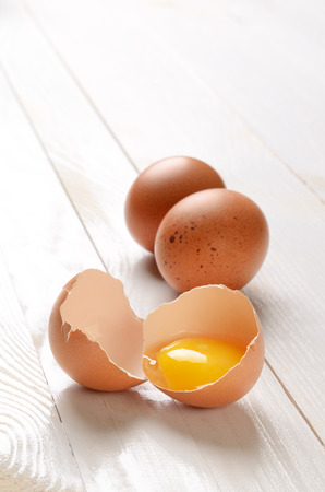 Broken egg on white wooden plank table Stock Photo