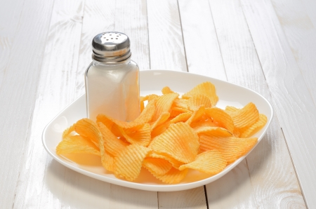 Potato chips on the plate with salt shaker on wooden table photo
