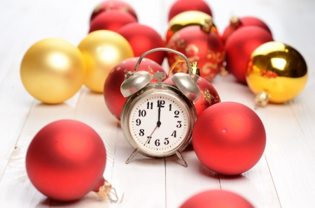 Alarm clock and christmas decorations on wooden plank table photo