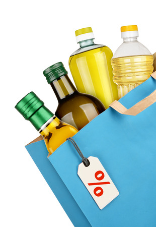 Grocery bag with oil bottles isolated on white background photo