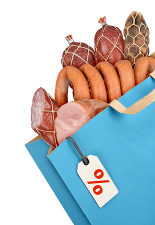 Grocery bag with sausages and meat isolated on white background photo