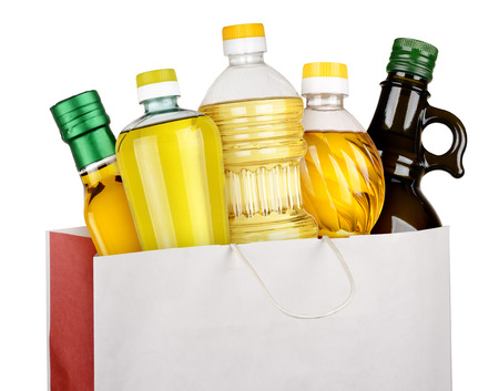 Oil bottles in paper bag isolated on white background photo