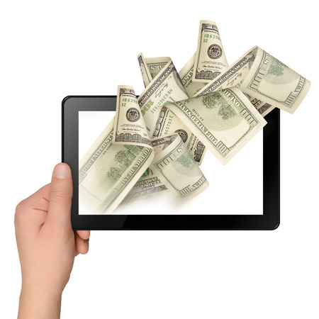 Hand holding a tablet with flying off money. Electronic business concept photo