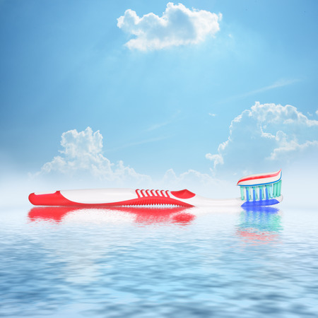 Toothbrush with toothpaste reflecting in water against sky background photo