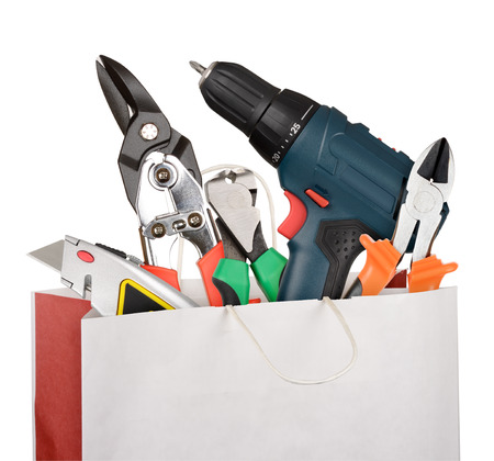 Shopping bag with a different work tools isolated on white background photo