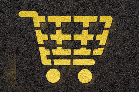 cart road: Asphalt road with yellow shopping cart symbol Stock Photo