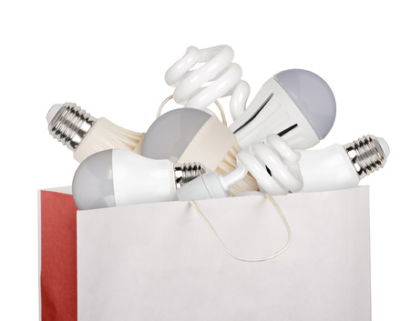 Shopping bag full of LED and fluorescent lamps isolated on white background photo